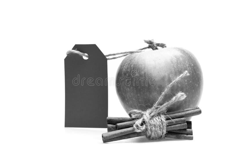 在白色背景和香料隔绝的苹果 套果子,肉桂条和倒空红色价牌 免版税库存照片