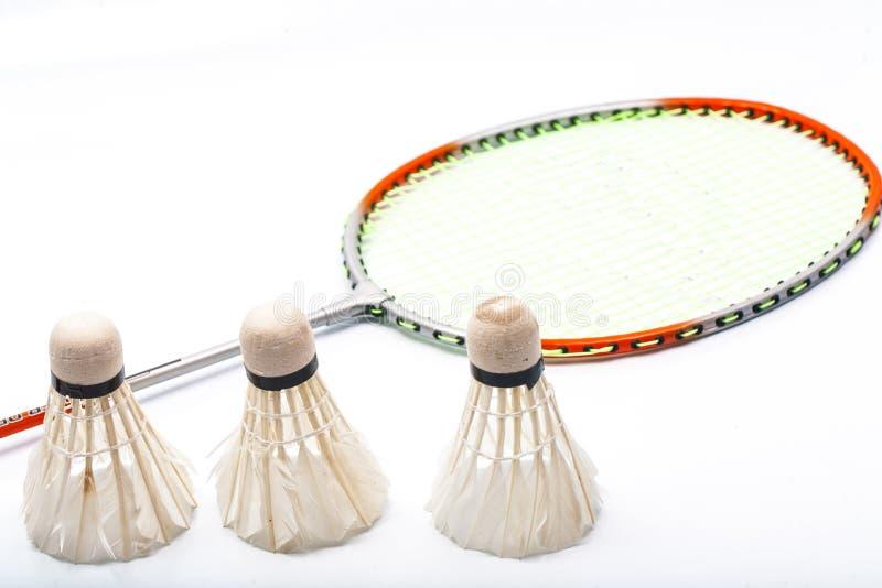 在白色背景和shuttlecock隔绝的羽毛球拍 库存照片