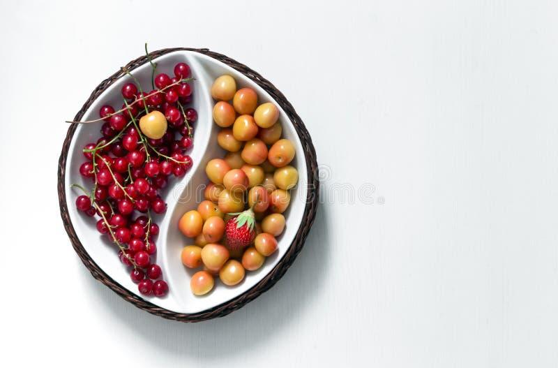 在白色背景圆的碗yin上杨用红浆果和草莓黄色樱桃绿色叶子夏天莓果  库存照片
