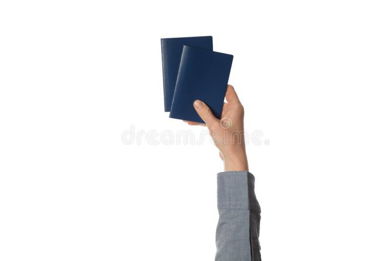 在白色背景在手中隔绝的蓝色护照 关税控制和旅行 免版税库存图片