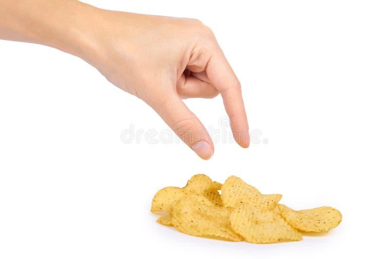 在白色背景在手中隔绝的鲜美波纹状的芯片,土豆片,不健康的食物,许多油脂和卡路里 库存照片