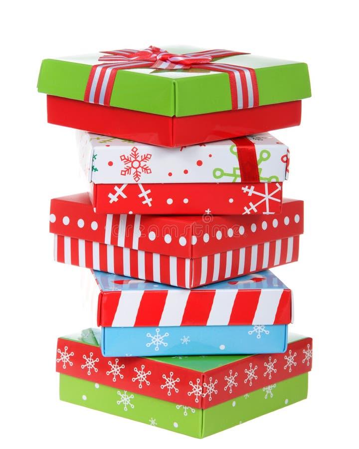 在白色背景堆积的明亮的圣诞节礼物 库存照片