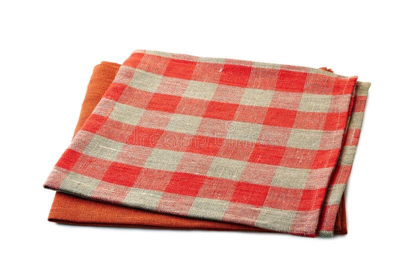 在白色背景堆积的红色和红方格的纺织品餐巾 免版税库存图片