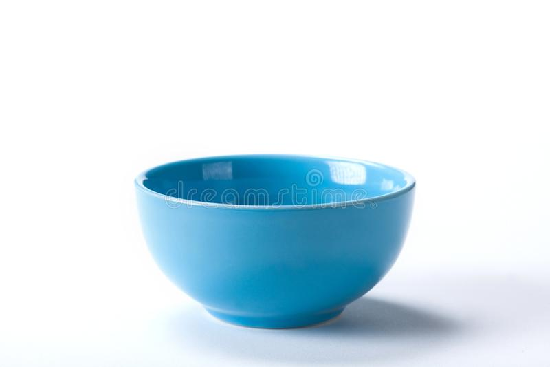 在白色背景射击隔绝的陶瓷蓝色碗的关闭在演播室 库存照片