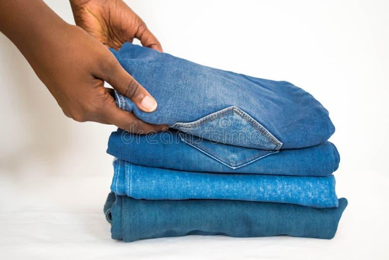 在白色背景或牛仔布隔绝的非洲妇女可折叠堆牛仔裤 图库摄影