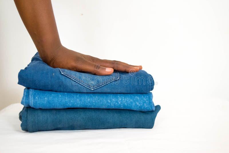 在白色背景或牛仔布隔绝的非洲妇女可折叠堆牛仔裤 库存图片