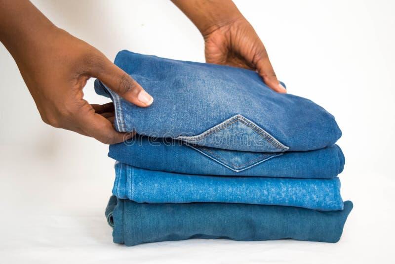 在白色背景或牛仔布隔绝的非洲妇女可折叠堆牛仔裤 免版税库存照片