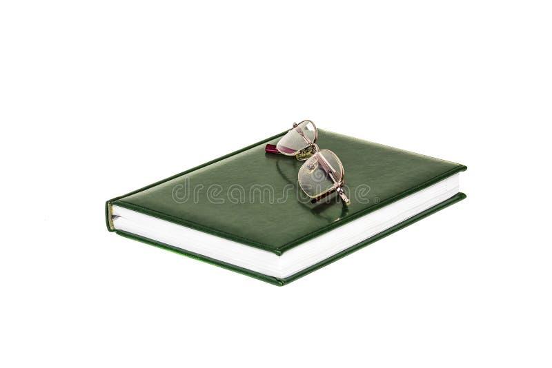 在白色背景是一本日志和玻璃眼睛的 免版税库存照片