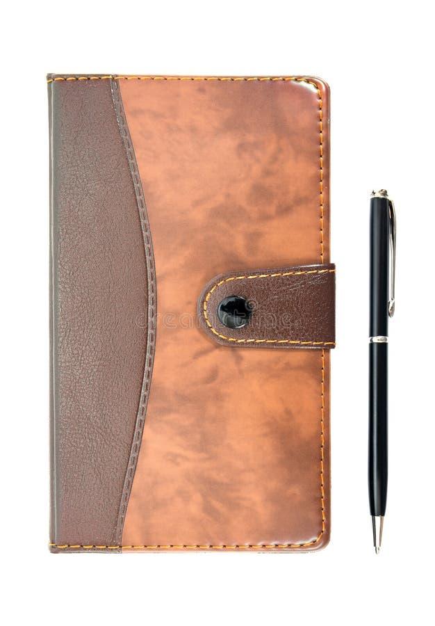 在白色背景有笔葡萄酒样式的布朗皮革笔记本隔绝的 有被隔绝的笔的皮革笔记本 免版税图库摄影