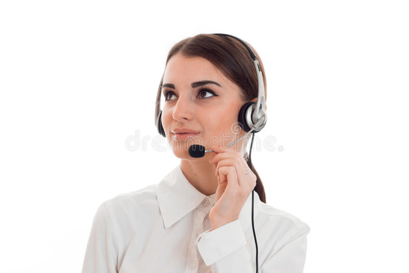 在白色背景有耳机和话筒摆在的隔绝的年轻美丽的电话中心工作者女孩画象  库存图片