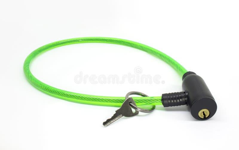 在白色背景有钥匙的绿色自行车缆绳锁隔绝的 免版税库存照片