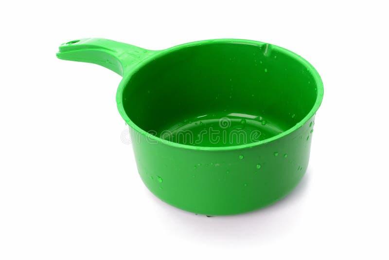 在白色背景有水下落的绿色塑料碗隔绝的 免版税图库摄影