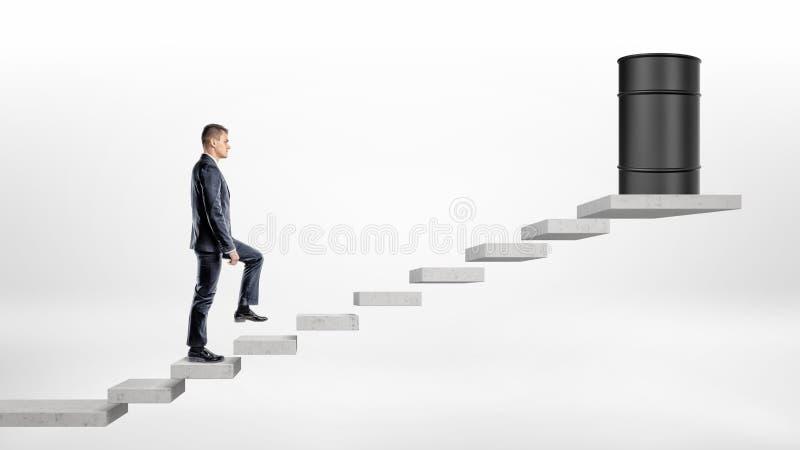 在白色背景的一个商人走一个黑油桶在上面站立的一个具体块台阶的 免版税库存图片