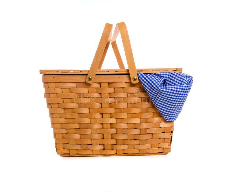 在白色背景的一个棕色柳条野餐篮子与方格花布布料 库存图片