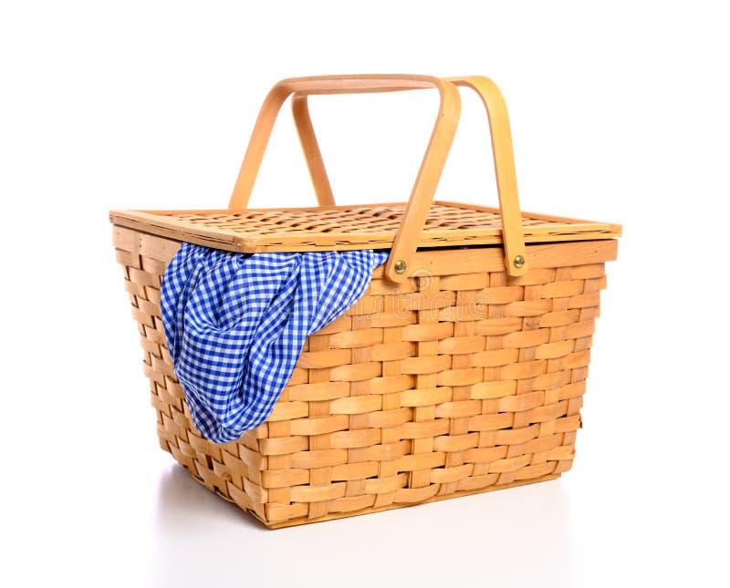 在白色背景的一个棕色柳条野餐篮子与方格花布布料 库存照片