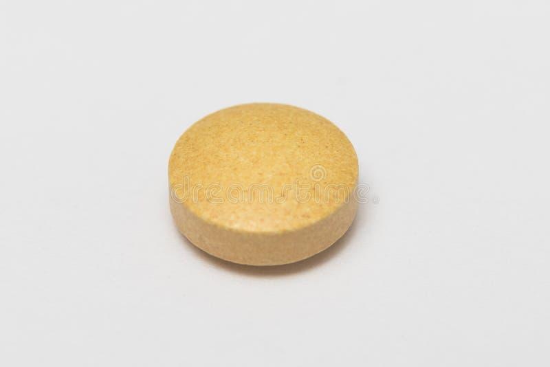 在白色背景的一个黄色药片 库存图片