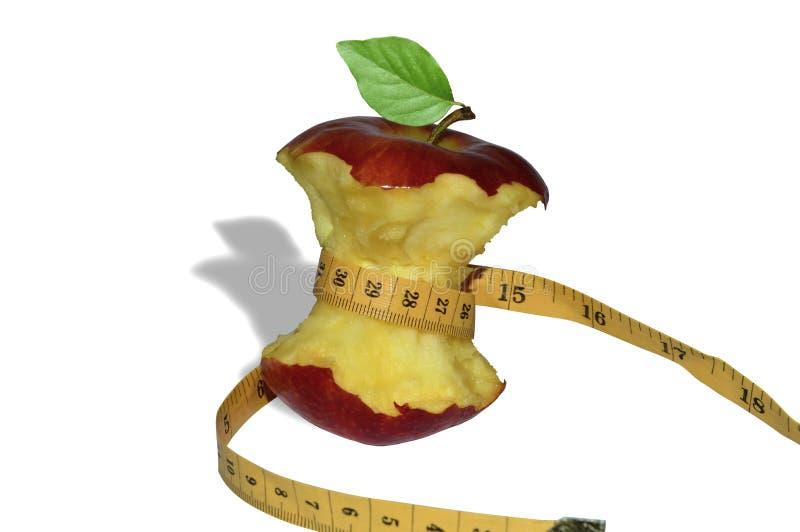 在白色背景的一卷测量的磁带包裹的一个红色苹果的核心 图库摄影