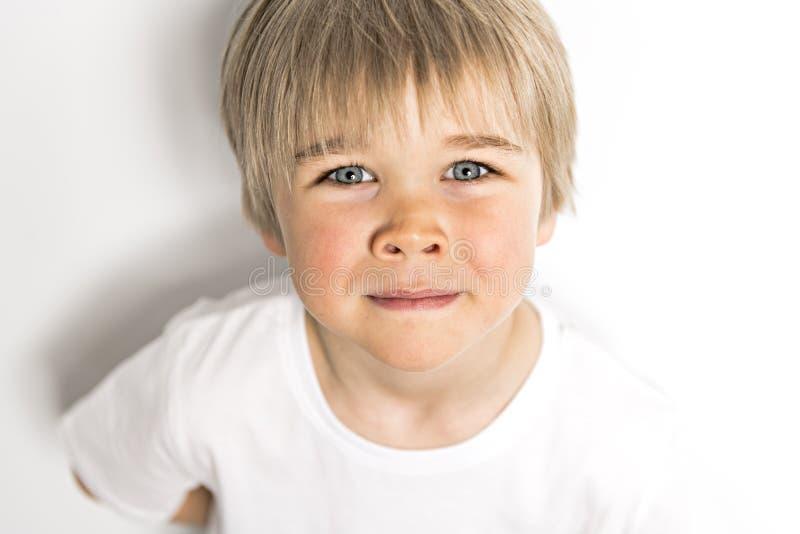 在白色背景的一张逗人喜爱的五岁的男孩演播室画象 免版税库存图片