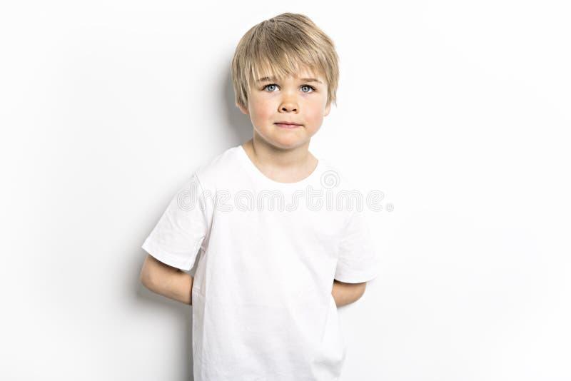 在白色背景的一张逗人喜爱的五岁的男孩演播室画象 库存照片