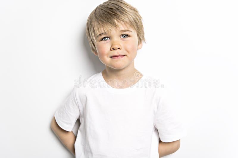 在白色背景的一张逗人喜爱的五岁的男孩演播室画象 免版税图库摄影