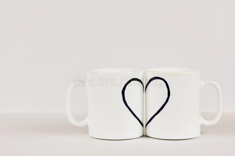 在白色背景的两个杯子画的心脏 情人节,爱,夫妇,婚姻的概念 库存图片