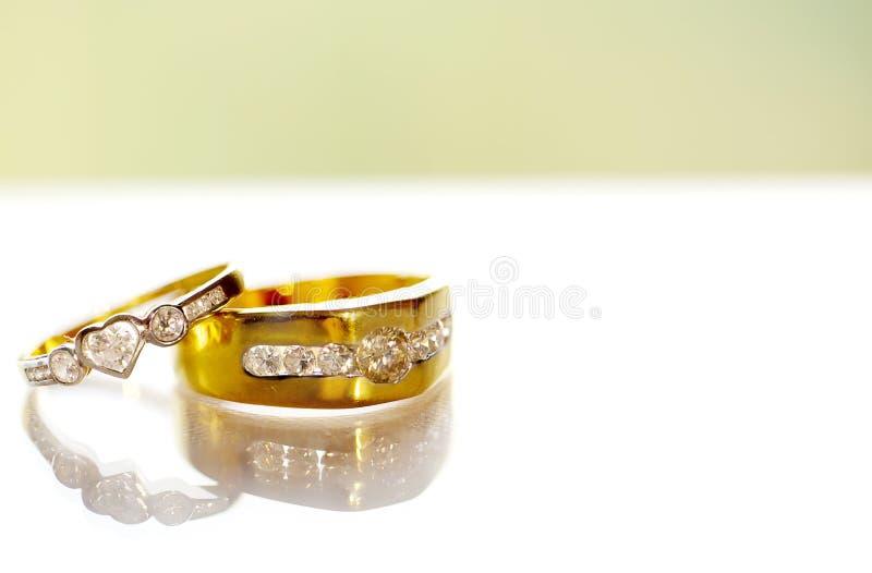 在白色背景的两个金钻石婚圆环 与金刚石的金婚圆环在白色背景 图库摄影