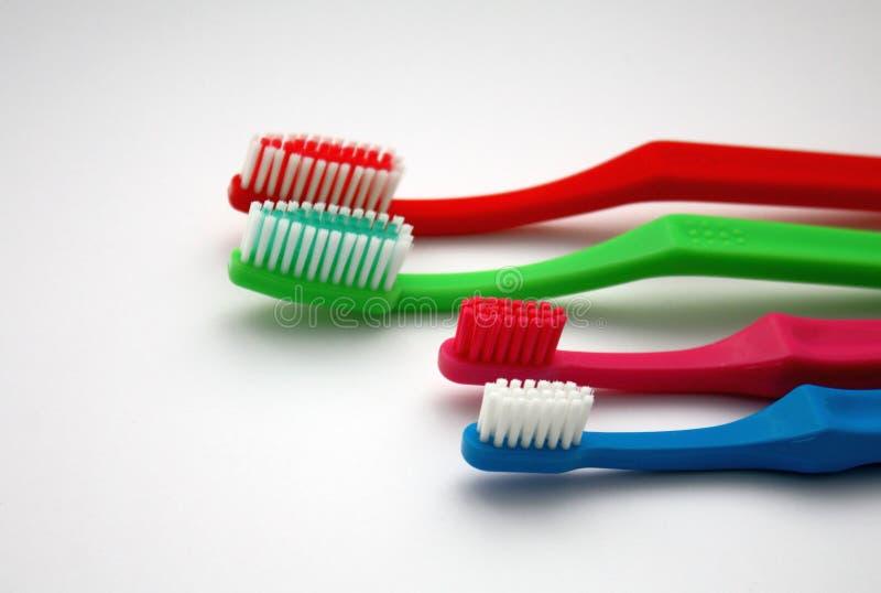 在白色背景的五颜六色的家庭牙刷,红色和绿色成人牙刷和桃红色和蓝色小两孩子的 免版税库存照片