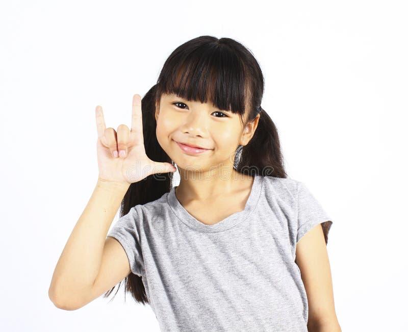 在白色背景的亚洲女孩展示爱标志手 免版税库存图片