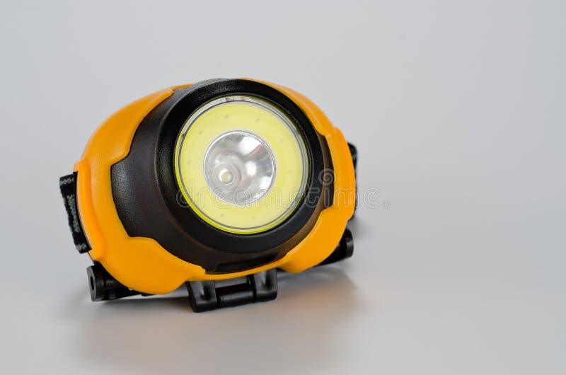 在白色背景的塑料LED头手电黑色黄色 库存照片