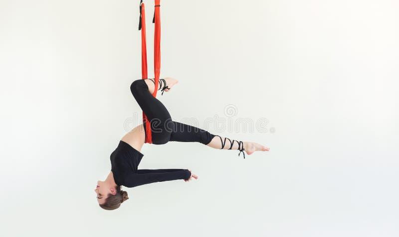 在白色背景的妇女实践的飞行瑜伽 图库摄影