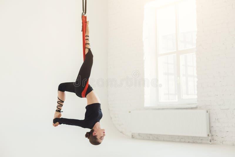 在白色背景的妇女实践的飞行瑜伽 库存图片