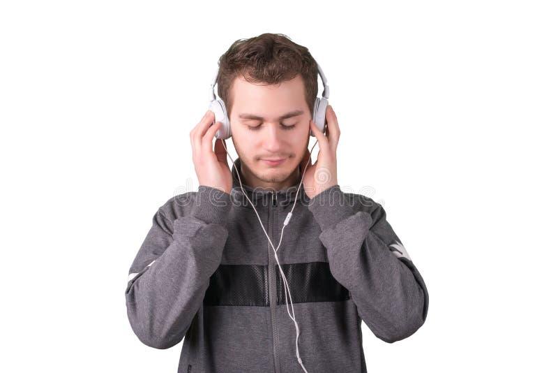 在白色背景的帅哥听的音乐 免版税库存照片