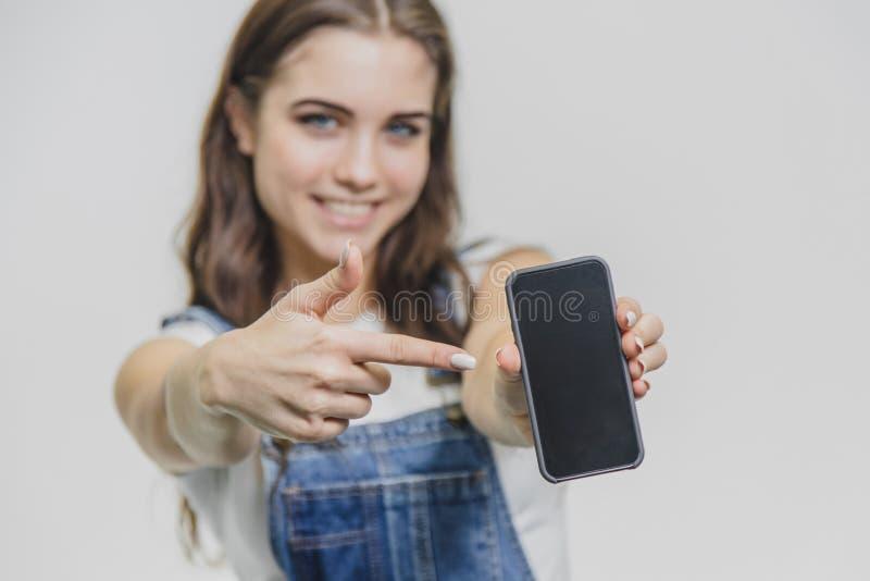 在白色背景的年轻俏丽的女孩身分 牛仔布总体的震惊美女 看照相机  免版税库存图片