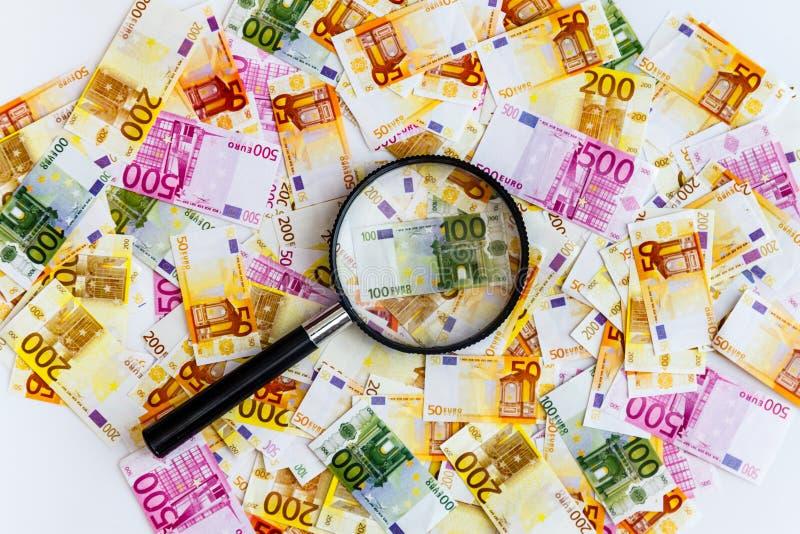 在白色背景的很多欧元钞票和在顶面,顶视图的一个放大镜 免版税库存图片
