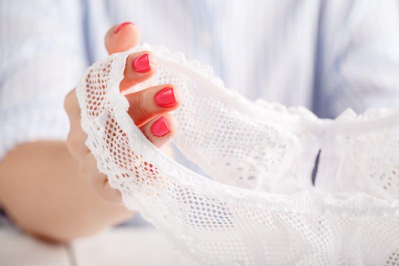 在白色背景的性感的透明内裤在女性手上 库存图片