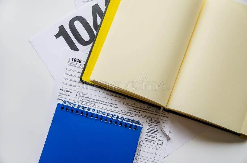 在白色背景的报税表1040和笔记本 库存图片