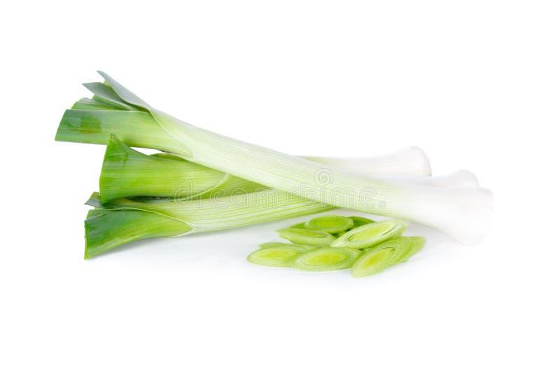 在白色背景的整个和切的新鲜的韭葱 库存图片