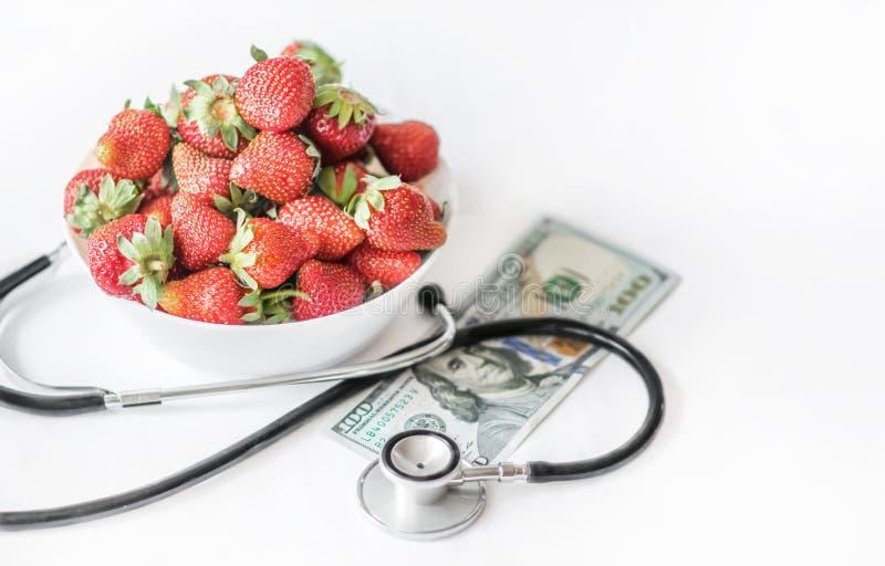 在白色背景的新鲜的夏天草莓与医疗听诊器和monye钞票一百美元 概念的他 免版税库存照片