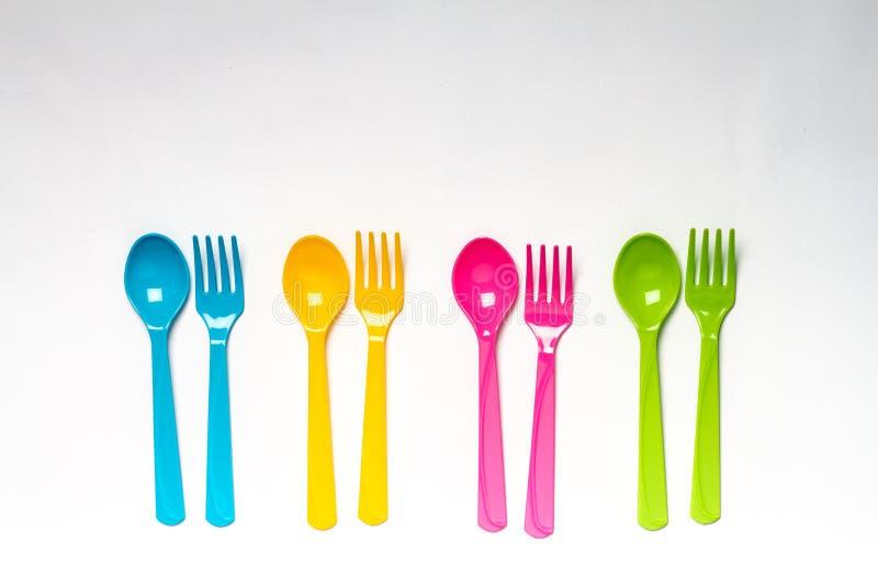 在白色背景的明亮的五颜六色的塑料一次性碗筷 库存照片