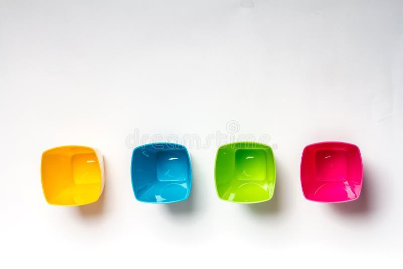 在白色背景的明亮的五颜六色的塑料一次性碗筷 免版税库存照片