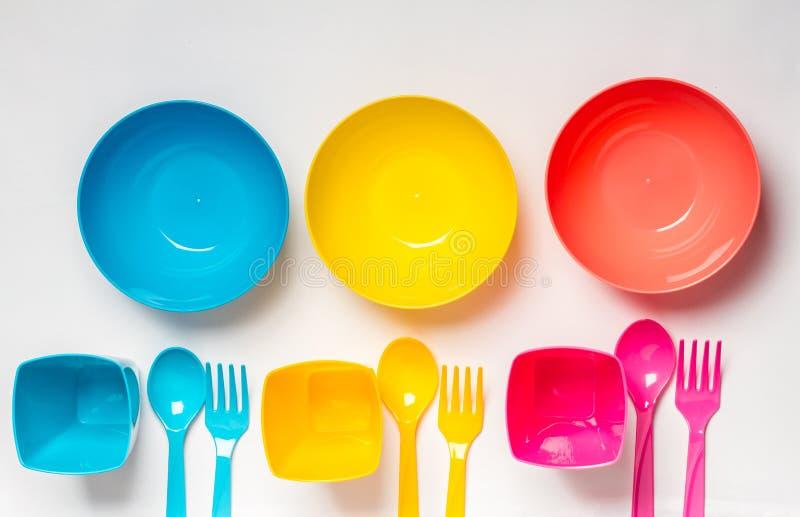 在白色背景的明亮的五颜六色的塑料一次性碗筷 图库摄影