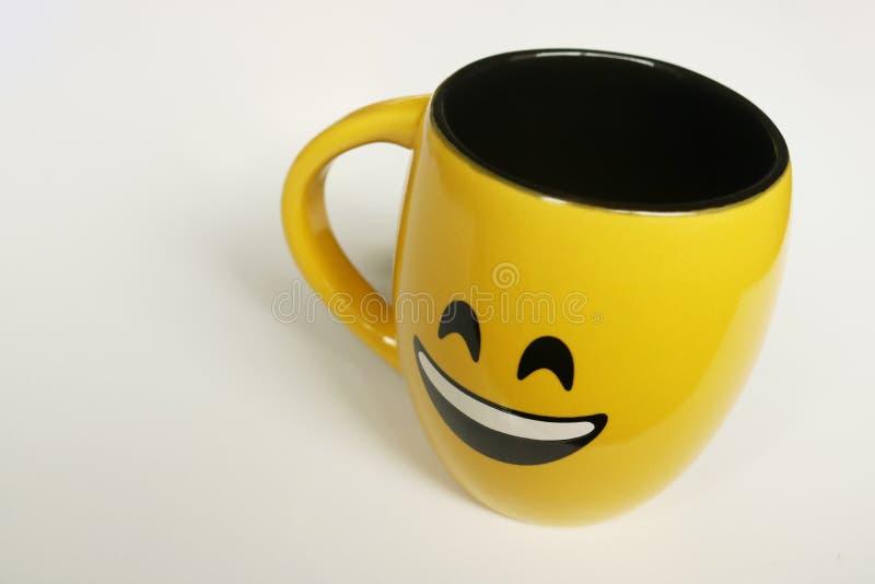 在白色背景的杯子与兴高采烈的面孔和黄色颜色 库存照片