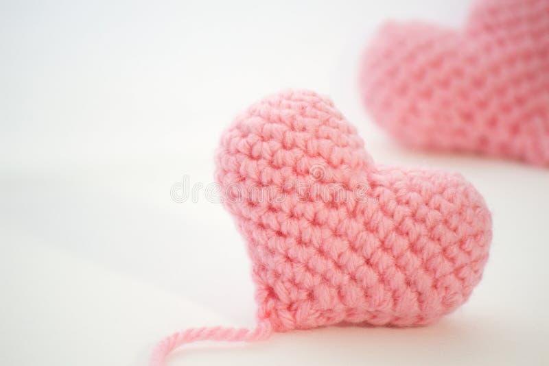 在白色背景的桃红色钩针编织心脏的迅速移动的图象 图库摄影