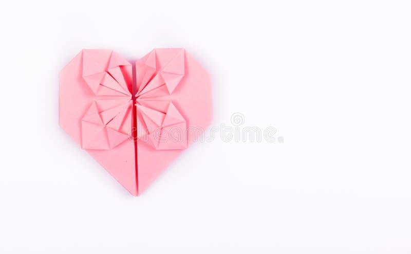 在白色背景的桃红色origami心脏 华伦泰由纸制成 免版税库存照片