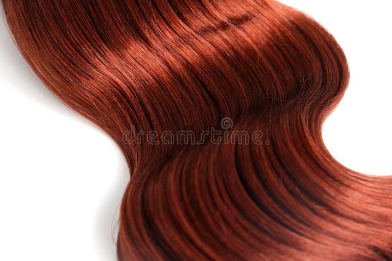 在白色背景的波浪红色头发 免版税库存图片