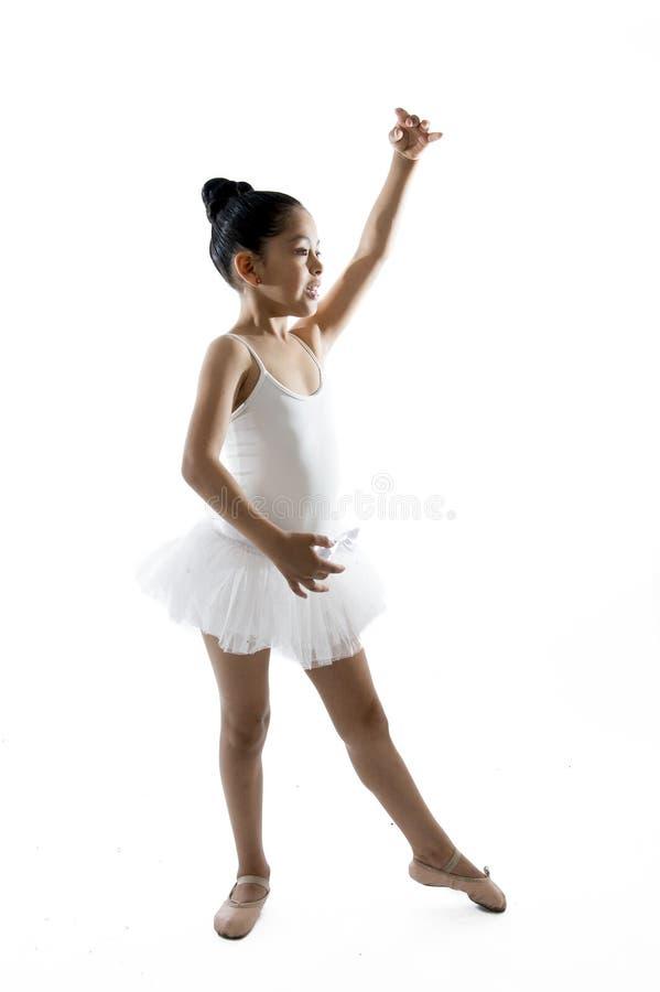 在白色背景的甜年轻矮小的逗人喜爱的跳芭蕾舞者女孩跳舞 免版税库存图片