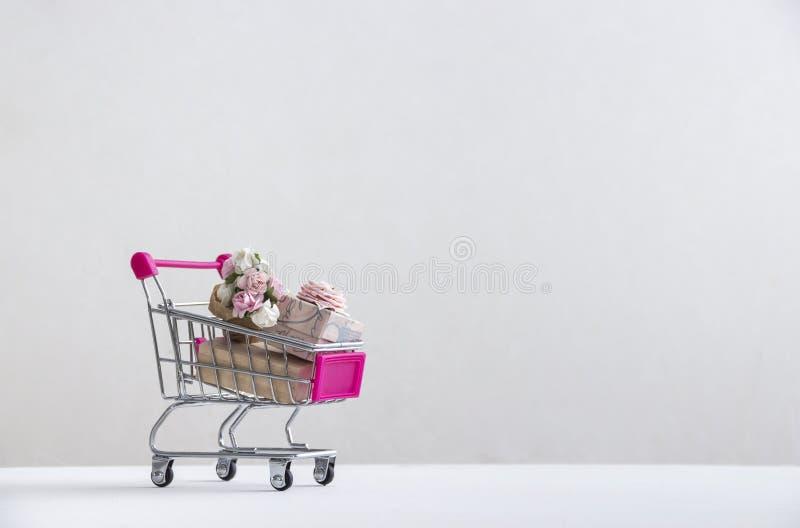 在白色背景的白色地板上有有一件桃红色礼物与弓和花玫瑰花束的一辆台车  库存图片