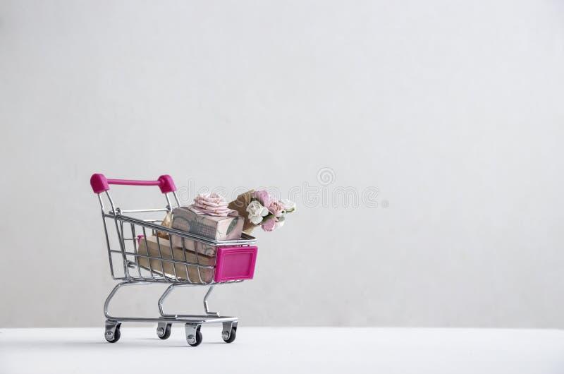 在白色背景的白色地板上有有一件桃红色礼物与弓和花玫瑰花束的一辆台车  免版税图库摄影