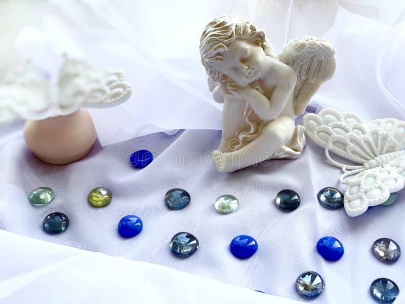 在白色背景的白色小男孩天使,海下落,绿松石,银,透明 白色蝴蝶 库存照片