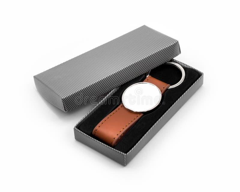 在白色背景的皮革钥匙圈 在包裹箱子的时尚钥匙链 纪念品或辅助部件 库存照片